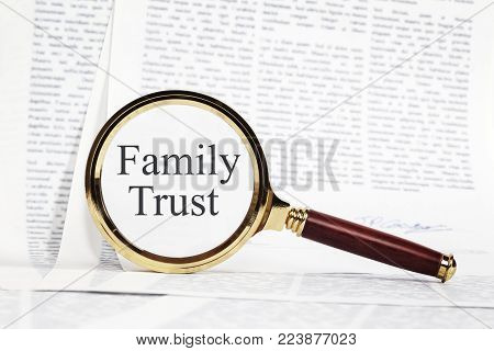 Family Trust Concept - paperwork representing a Family Trust, with a magnifying glass over, highlighting Family Trust.
