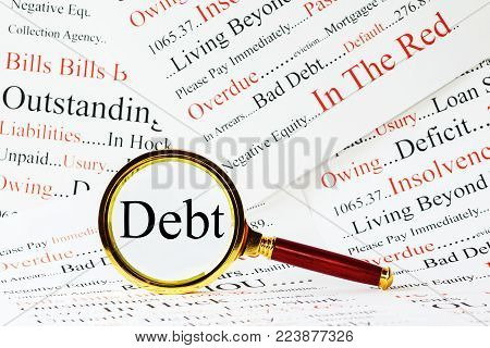 Debt Concept - magnifying glass over the word Debt, with a background of words associated with debt.