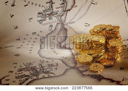 Doubloons and Treasure Map - Old map of Atlantis and a pile of gold doubloons.