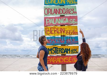 One guy and redhead girl possing over directions signpost on the beach.