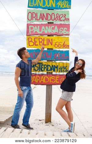 Casual man in denim jeans and redhead woman posing near world towns signpost.