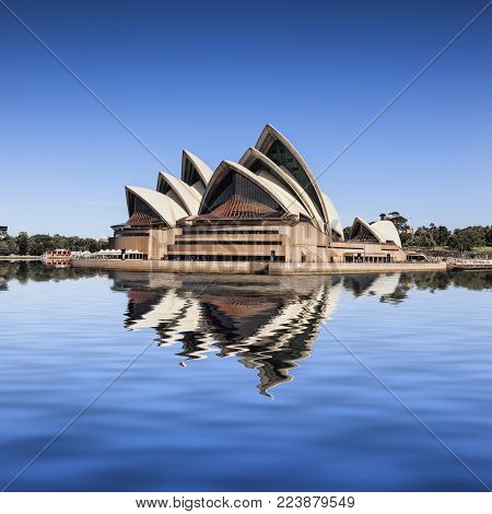 14 March 2014: Sydney, Australia - Sydney Opera House, viewed from a passing boat, reflected in Sydney Harbour.