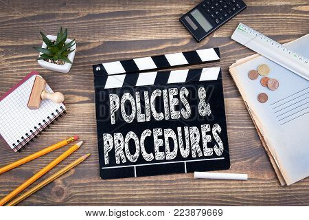 Policies and Procedures. movie clapper on a wooden desk.