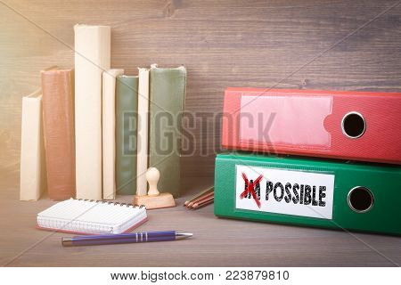 Change impossible to possible. Binder on desk in the office. Business background.