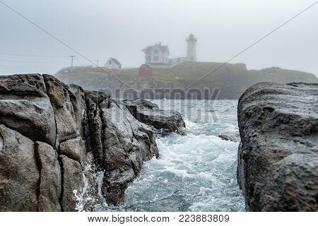Water Rushes Through Rocks at Cape Neddick Lighthouse along Maine's coast