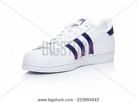 LONDON, UK - JANUARY 24, 2018: Adidas Originals Superstar blue shoes on white background.German multinational corporation that designs and manufactures sports shoes, clothing and accessories.