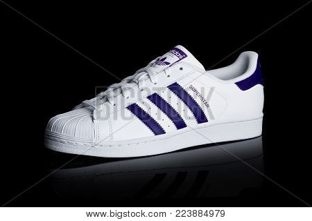LONDON, UK - JANUARY 24, 2018: Adidas Originals Superstar blue shoes on black background.German multinational corporation that designs and manufactures sports shoes, clothing and accessories.
