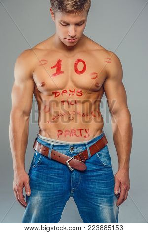 Shirtless muscular young guy with text on his torso. Isolated on grey torso.