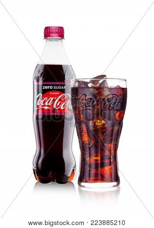 LONDON, UK - JANUARY 24, 2018: Bottle and glass of Zero Cherry Coca-Cola on white Background. Coca-Cola is one of the most popular soda products in the world.