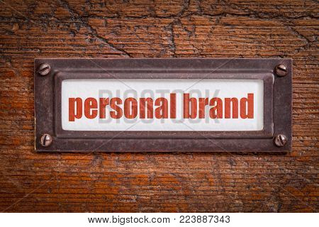 personal brand tag - file cabinet label, bronze holder against grunge and scratched wood
