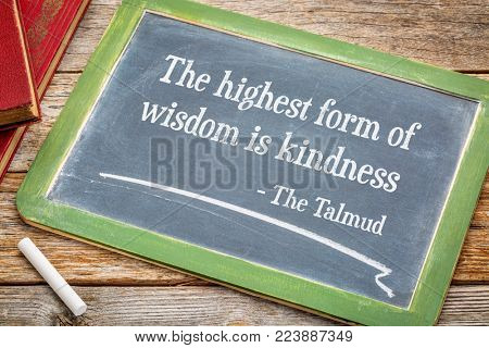 The highest form of wisdom is kindness, Talmund quote - white chalk text on a slate blackboard