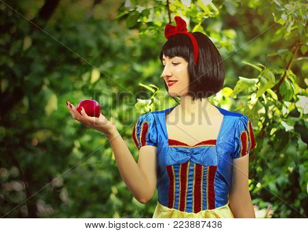 Young beautiful snow-white close-up keeps a red poisoned apple against the background of trees in the forest.