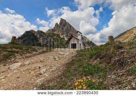 Small white chapel with Sass de Stria mountain on top of Falzarego pass in the Dolomites, Italy