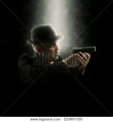 Man holding gun with a finger on the trigger. Soft focus
