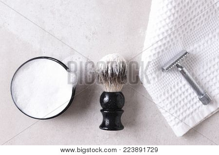 Shaving Still Life: Safety razor on a towel with brush and soap on a gray tile surface.