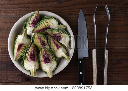 Artichokes: Sections of a cut artichoke on a plate ready to be grilled, a knife and tongs round out the scene.