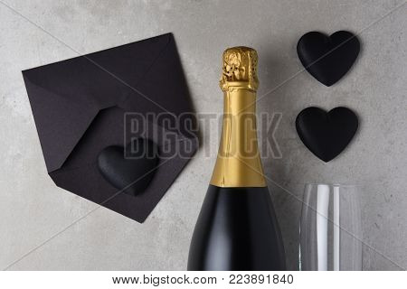 Valentines Day: Black hearts and black envelope next to an unopened bottle of Champagne.