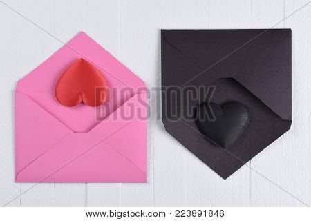 Valentines Day Concept: A pink envelope with a red heart next to a black envelope with a black heart. White wood background.