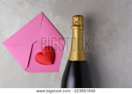 Valentines Day: Pink envelope and red heart next to a bottle of champagne, with copy space.