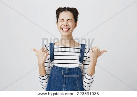 Portrait of a happy young brunette woman giving two thumbs up gesture with closed eyes and clenched teeth in full disbelief isolated against grey wall background. Positive human emotions, facial expressions and body language.