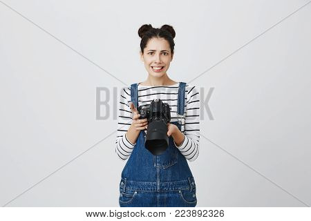Puzzled confused european brunette female photographer with two hairbuns wearing denim overall using modern camera. Woman with clenched teeth in confusion holding photo camera, thinking about next step