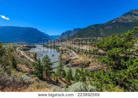 View of beautiful landscape in the Rocky Mountains with fresh blue and green mountain river water and mountain tops in the background on a sunny day with blue sky in springtime.