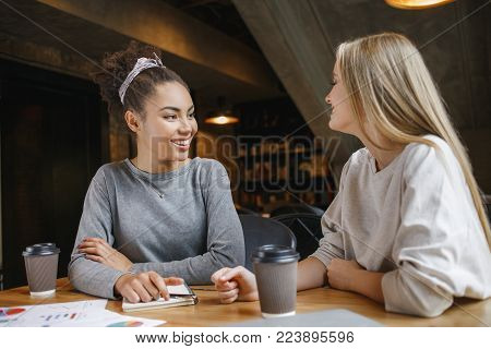 Young women students having a business lunch drinking hot coffee doing project discussion looking at each other smiling joyful