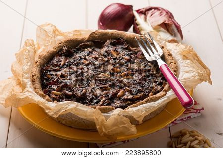 cake with chicory onions and pine nuts, selective focus
