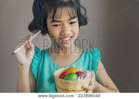 Cute little child on Easter day.Girl holding basket with painted eggs.