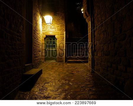 a stone paved alley in Mont St. Michel at night