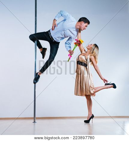 Young man and woman pole dancers. Man giving flowers to woman. Love concept.