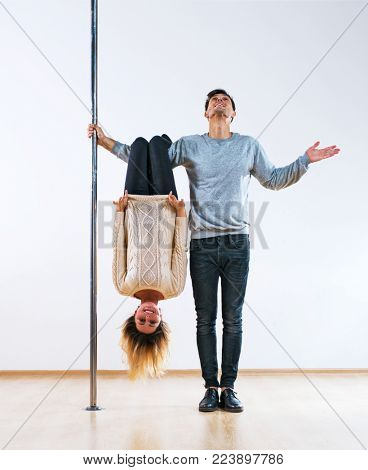Young man and woman pole dancers in casual clothing happy emotions