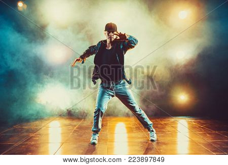 Young man break dancing in club with lights and smoke