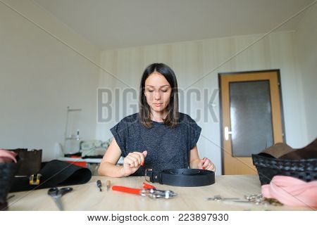 Sales manager working in firm dealing with leather products making list of produced bags, wallets and belts in notebook. Young woman sitting near table with tools and purses, sorting things and making notes. Concept of business, leather industry or trade.