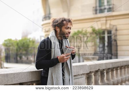 Handsome mix blood boy typing message and listening to music with white in ear headphones near Eiffel tower. Young guy wears in fashion clothes has beard and long fleecy hair. Concept of autumn in Paris, using modern technologies and fast Internet connect