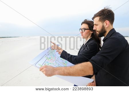 Deputy female and architect male meet to discuss stadium in countryside, people standing in deserted place holding whatman paper with plan smiling looking around. Young bearded man in black shirt and lady in glasses wearing strict suit communicating. Conc