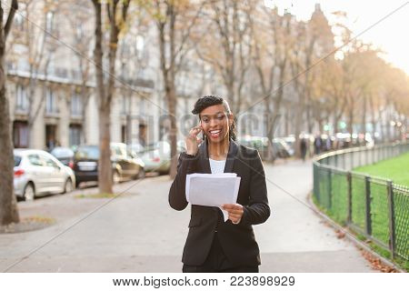 Online store consultant speaking with customers by smartphone during walk outdoors. Young  woman dressed on black suit looks confident and purposeful. Concept of working in open air using mobile phone for consulting people.