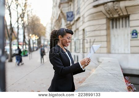 Welcoming insurance agent had good deal with rich client. African American discussing work using silver smartphone and walking on bridge with papers in hands. Black-haired lady with beautiful hair styling wearing black suit and white blouse. Young woman r