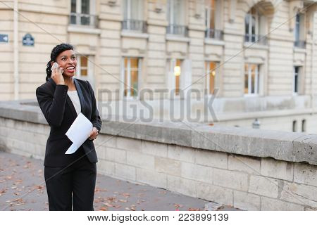 Volunteer with documents in hands discussing details with sponsor for charity concert using smartphone. Benevolent African American standing on street near old buildings and talking on phone. Neat black-haired female with beautiful hair styling wearing wh