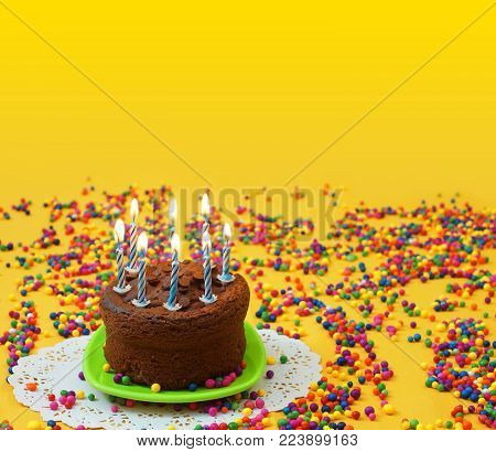 Chocolate birthday cake with lighted blue and white candles, on a small green plate surrounded by candy balls strewn on a yellow background. Image with copy space