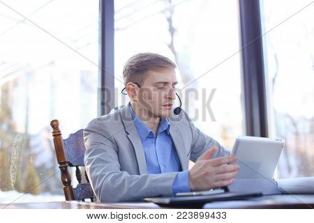 Businessman making video call using tablet, headset phones with microphone and talking with architect about draft roll project. Young man sitting at cafe and working. Concept of construction company and working at break.
