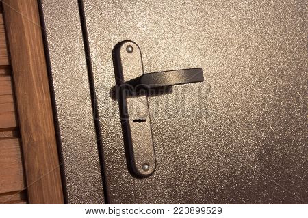 door handle. close up. dark door. the door is closed.