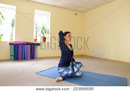Sportswoman focused on stretch before Pilates class. Girl doing warm up for legs on mat. Female has hair pulled back, concentrated look. Athlete dressed in dark top, yoga legging trains in fitness room. Concept of online training, customizable workouts.