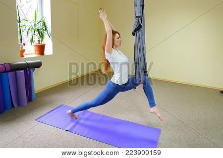 Beautiful girl of American appearance performs acrobatic elements in air, child concentrates and calmly holds on acrobatic ropes.