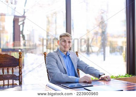 Interior designer using smart watch at cafe with tablet and roll project on table. Young handsome man waiting for business meeting. Concept of enhancing interiors of space or building to achieve healthier and more aesthetically pleasing environment for us