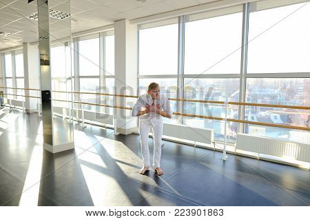 Street style dancer doing hand vigorous actions near windows. Blonde guy wears white suit. Concept of energetic exercises for improving dancing technique.