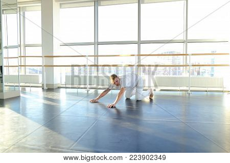 Young dancer doing close up backwards somersault . Male person training at gym studio. Concept of advertisement of dance school and successful graduates.