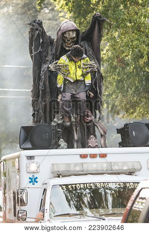 ATLANTA, GA - OCTOBER 2017:  Animatronic demons grab at a lifelike ambulance driver as part of a haunted house promotion at the Little Five Points Halloween Parade in Atlanta, GA on October 21, 2017.