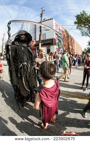 ATLANTA, GA - OCTOBER 2017:  A boy interacts with person wearing menacing grim reaper costume and holding scythe, before the start of the annual Little Five Points Halloween Parade in Atlanta, GA on October 21, 2017.