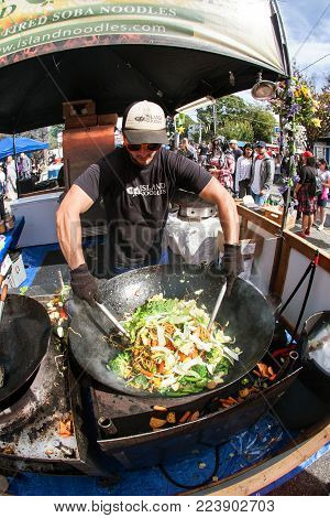 ATLANTA, GA - OCTOBER 2017:  A restaurant employee mixes noodles and vegetables together in a huge wok, preparing stir fry dishes for patrons at the Little Five Points Halloween parade in Atlanta, GA on October 21, 2017.